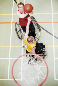 wheelchair bound men play basketball underneath the hoop. Shot from above.